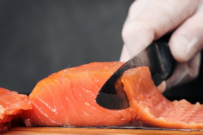 r?ka kucharz?w zako?czenie Szef kuchni ciie z nożem czerwonej ryby, uwędzony łosoś na drewnianej tnącej desce fotografia royalty free