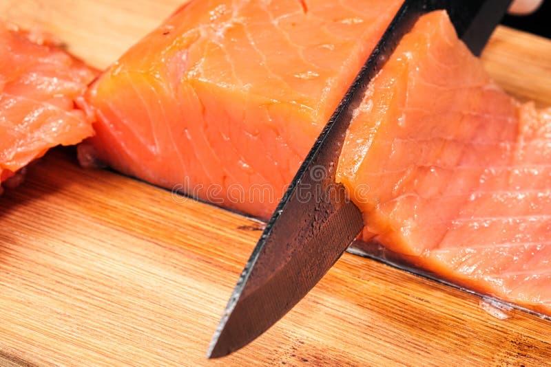 r?ka kucharz?w zako?czenie Szef kuchni ciie z nożem czerwonej ryby, uwędzony łosoś na drewnianej tnącej desce zdjęcia royalty free