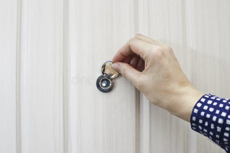 R?ka otwiera drzwiow? peephole pokryw? w dzwi wej?ciowy zdjęcie stock