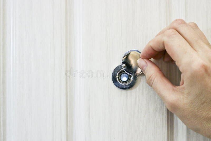 R?ka otwiera drzwiow? peephole pokryw? w dzwi wej?ciowy obrazy stock