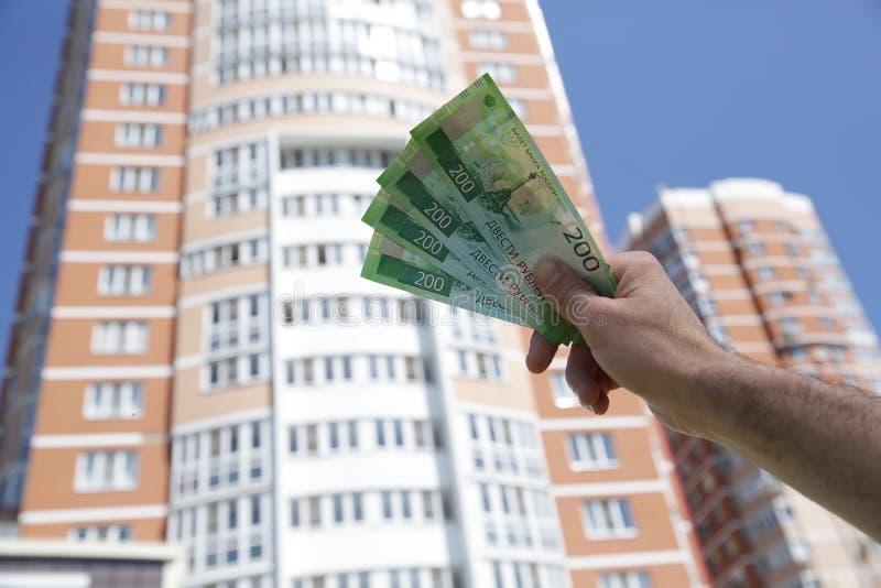 R?ka trzyma nowego Rosyjskiego banknot dwie?cie rubli na tle du?y budynek niebieskie niebo i Got?wkowy papierowy pieni?dze zdjęcia royalty free