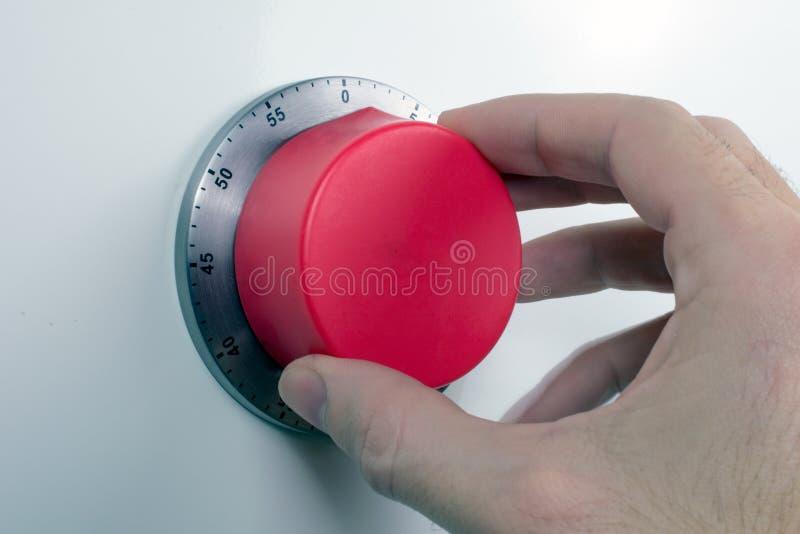 R?ka wszczyna czerwonego kuchennego zegar obraz royalty free