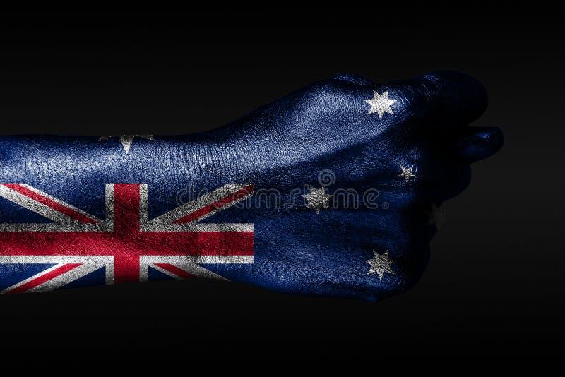 R?ka z maluj?c? Australia flag? pokazuje figi, znak agresja, nieporozumienie, sp?r na ciemnym tle zdjęcie royalty free