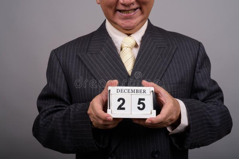 R?ki dojrza?y Azjatycki biznesmen trzyma kalendarzowych blok?w agains obraz stock