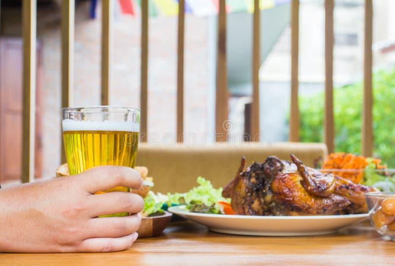 R?ki mienia piwo Łomotający pojęcie Z kurczaka prażakiem, sałatkowy francuz smaży na drewnianym obrazy royalty free