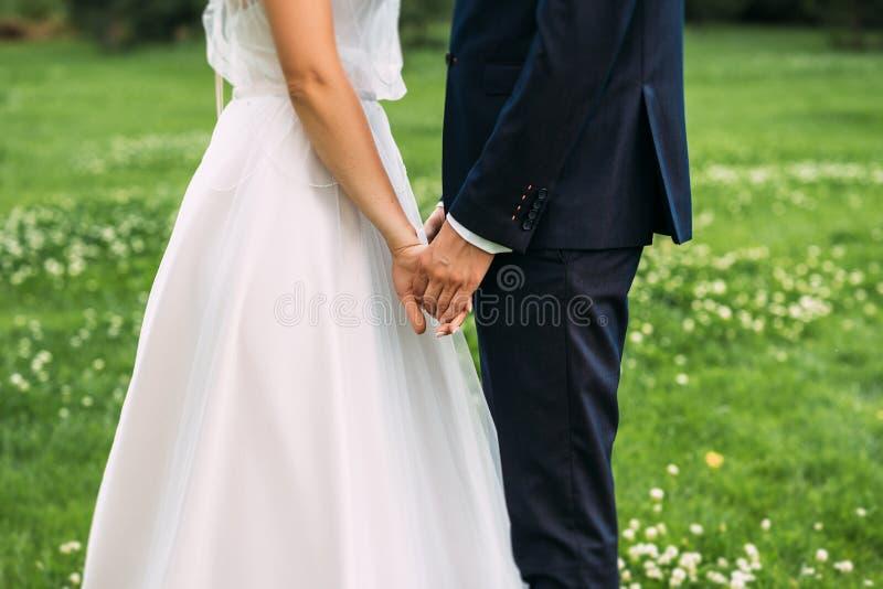 R?ki pa?stwo m?odzi Nowe potomstwo pary mienia ręki po ich ślubu M?ode pary ma??e?skiej mienia r?ki, ceremonia ?lub zdjęcia royalty free
