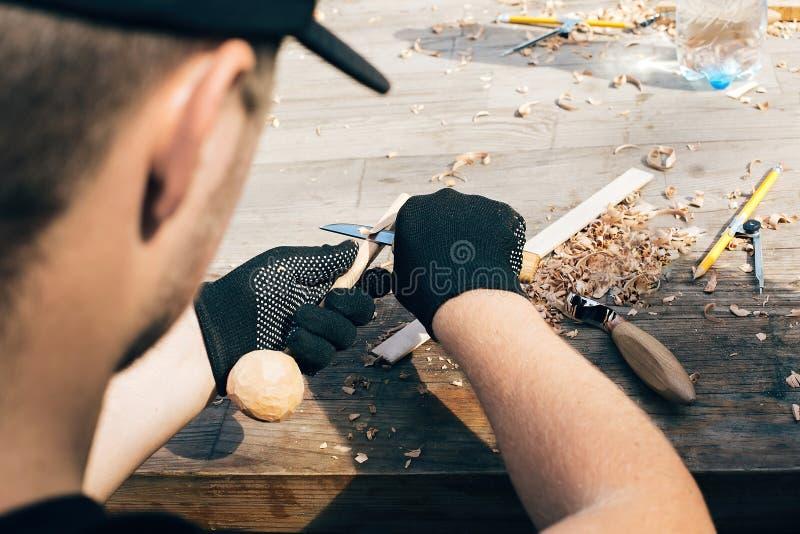 R?ki rze?bi ?y?k? od drewna, pracuje z ?cinakiem zamkni?tym w g?r? Drewniany warsztat Proces robi? drewnianej ?y?ce, ?cinak, o??w fotografia stock
