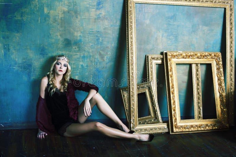R?knar samman den b?rande kronan f?r den unga blonda kvinnan i felik lyxig inre med tomma antika ramar rikedombegrepp fotografering för bildbyråer