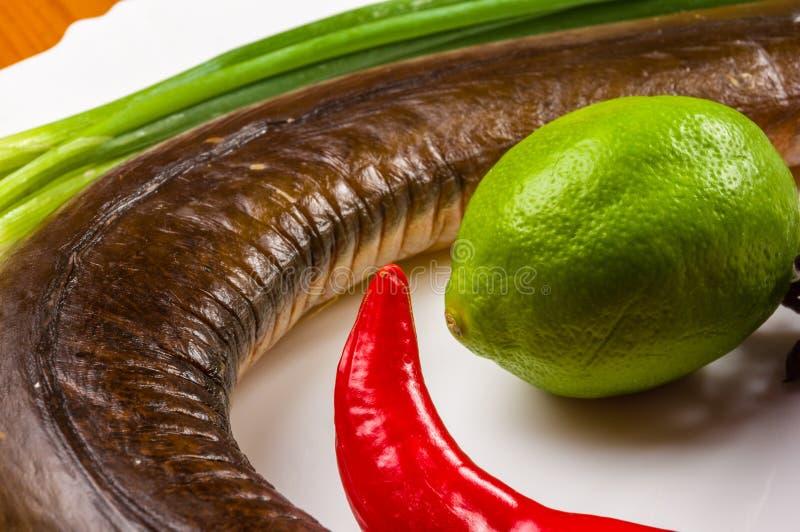 R?kt garfish med limefrukt, basilika, salladsl?kar, chili, norichiper, kryddor, olivolja i en vit keramisk matr?tt, p? ett tr? arkivfoton