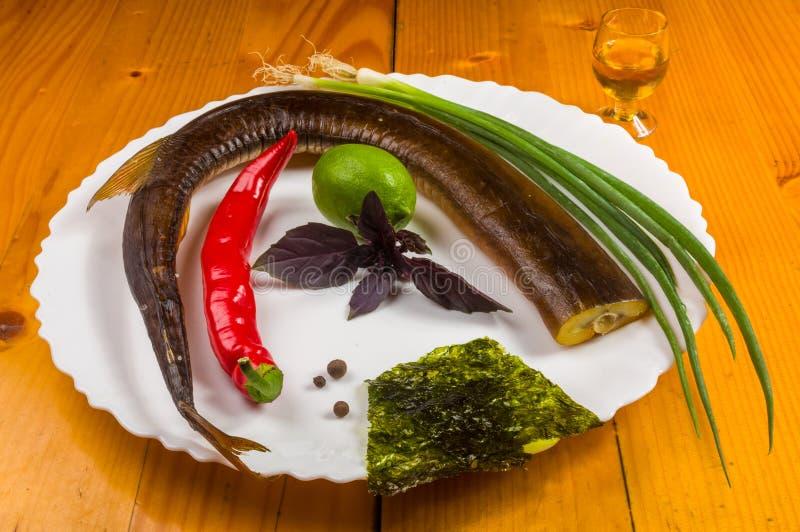 r?kt garfish med limefrukt, basilika, salladsl?kar, chili, norichiper, kryddor, olivolja i en vit keramisk matr?tt, p? en tr?tabe arkivbild