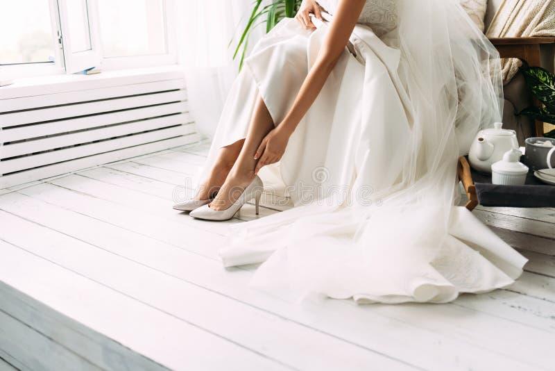 r laddningar av bruden Closeupdetalj av bruden som sätter på den höga heeled sandalen royaltyfria foton