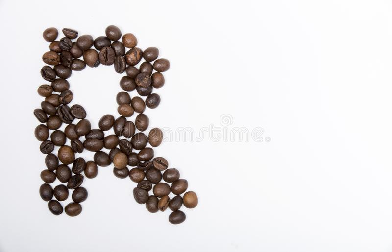 R - large letter of english alphabet. Made up of unmolished roasted coffee beans on a white background royalty free stock images