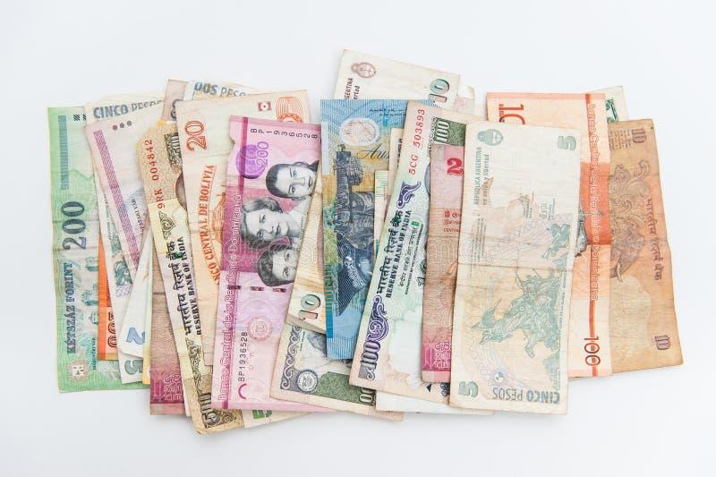 R??ni banknoty rozprzestrzeniaj?cy na bia?ym tle od po na ca?ym ?wiecie obraz stock