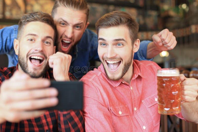 R??norodni fan pi?ki no?nej ogl?da futbol na smartphone i ?wi?tuje zwyci?stwo wynika w pubie obrazy royalty free