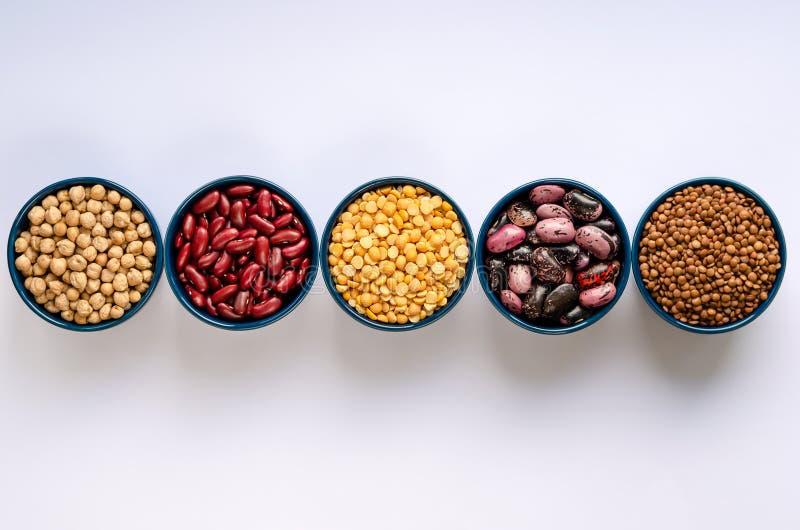 R??norodno?? Legumes Soczewicy, chickpeas, grochy i fasole w b??kitnych pucharach na bia?ym tle, Odg?rny widok zdjęcie stock
