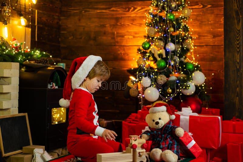 r r o Детская игра мальчика около рождественской елки r стоковая фотография