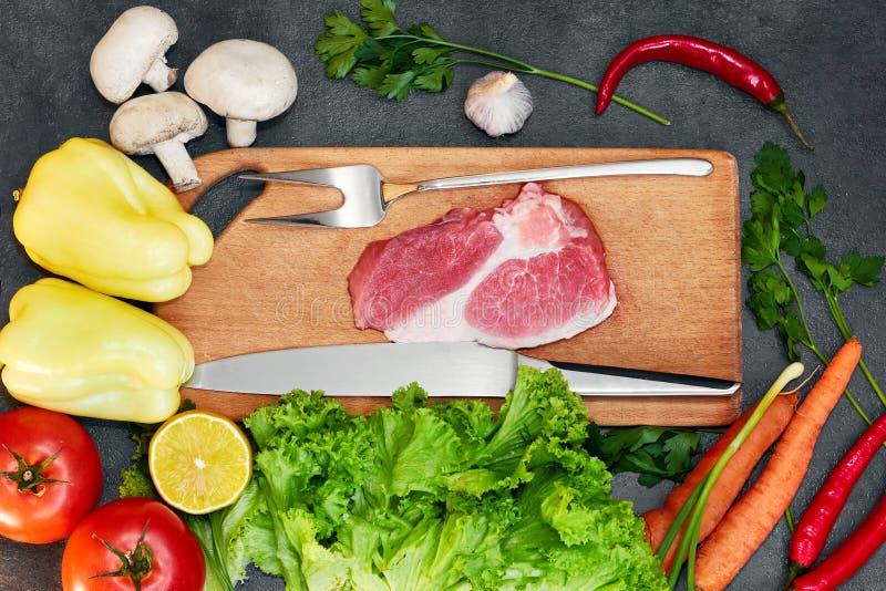R? organiska gr?nsaker med nya ingredienser f?r sund matlagning p? m?rkt backgroundRawk?tt Rå nötköttbiff på wi för en skärbräda arkivfoton