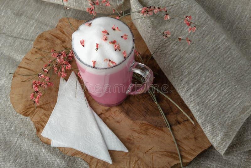 R??owy kawowy latte macchiato w szklanej fili?ance na drewnianym wsparciu dekoruj?cym z wysuszonym kwiatem obraz stock