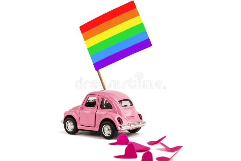 R??owy retro zabawkarski samoch?d dostarcza jaskraw? t?cza homoseksualisty flag? Poj?cie homoseksualna parada, LGBT spo?eczno?? i zdjęcie stock
