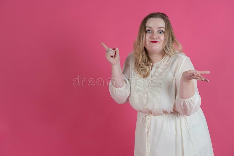 R??owy t?o Plus wielkościowa dziewczyna w białej sukni z jaskrawymi czerwonymi wargami pokazuje palec na przestrzeni i zaskakuje  zdjęcia royalty free