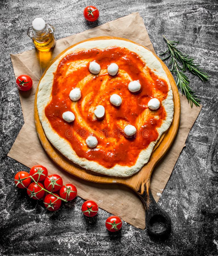 R? pizza Rullande ut deg med mozzarella- och tomatdeg arkivbild
