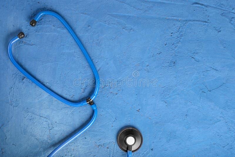 r Primo piano dello stetoscopio su un fondo di pietra blu Ascolti il cuore con lo stetoscopio Copi lo spazio per fotografia stock libera da diritti