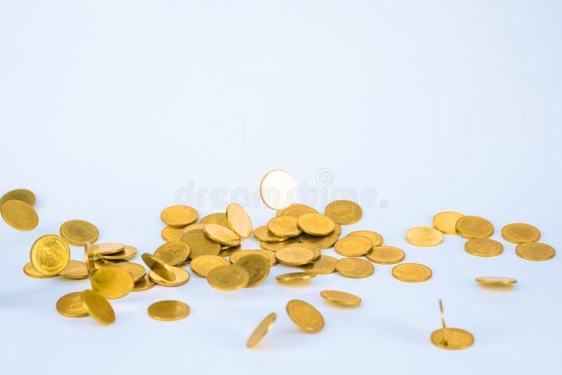 R?relse av det fallande guld- myntet, flygmyntet, regnpengar med mjuk skugga p? vit bakgrund, aff?ren och finansiell rikedom och arkivfoto