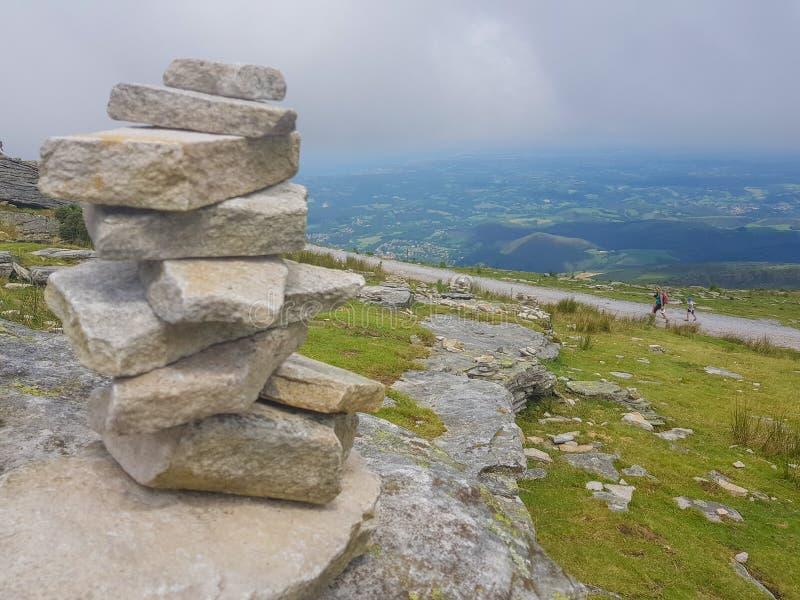 r?se ( Inukshuk rocks) upptill av det LaRhune berget i de atlantiska Pyreneesna Gr?ns mellan Spanien och Frankrike arkivbild