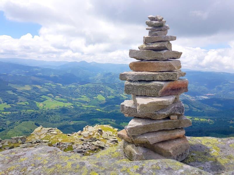 r?se ( Inukshuk rocks) upptill av det LaRhune berget i de atlantiska Pyreneesna Gr?ns mellan Spanien och Frankrike royaltyfria bilder