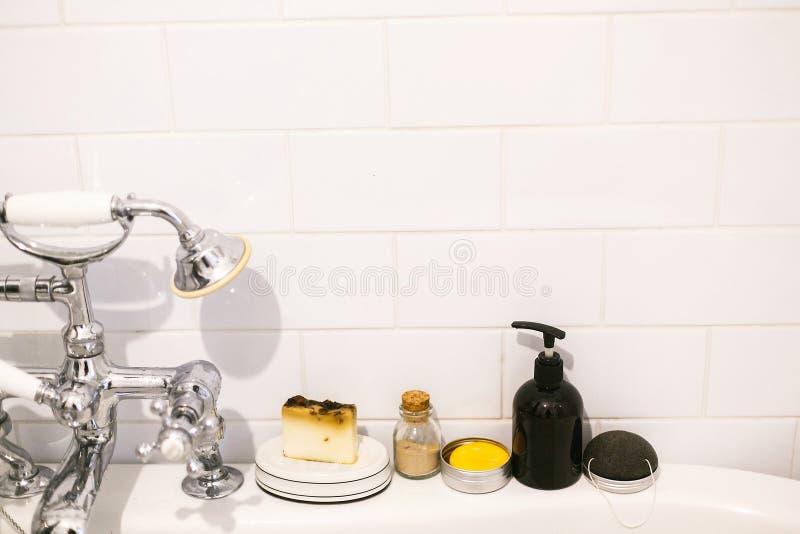 r Shampooing solide naturel d'Eco, poudre ubtan konjac d'?ponge, de savon et d'ayurveda en verre sur la baignoire dedans image libre de droits