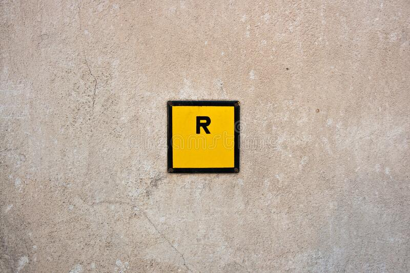 R sign in yellow square stock image