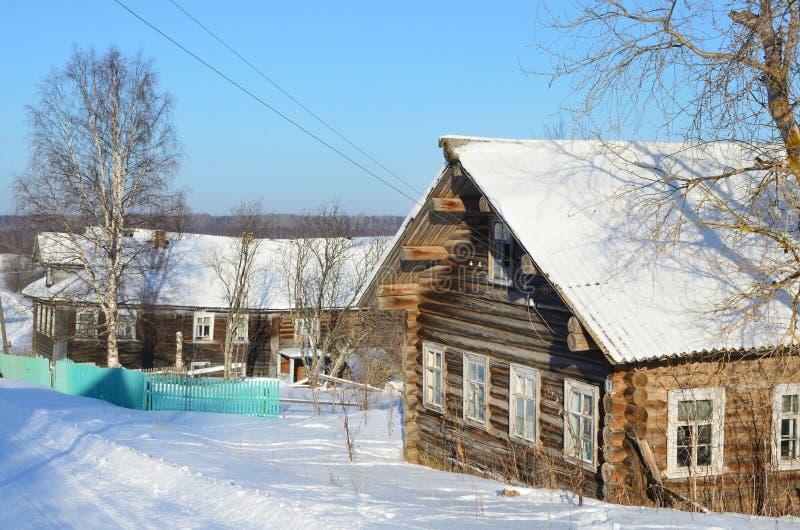 R?ssia, regi?o de Arkhangelsk, constru??es de madeira na vila Turchasovo no inverno no tempo ensolarado imagens de stock
