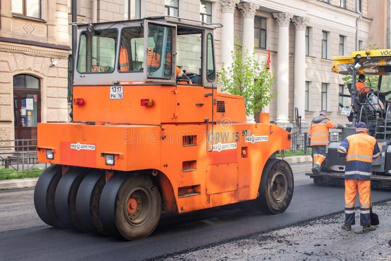 R?SSIA, ST PETERSBURGO - 12 DE MAIO DE 2019: Reparo das estradas Dois pavers e trabalhadores alaranjados do asfalto nas combinaçõ fotografia de stock