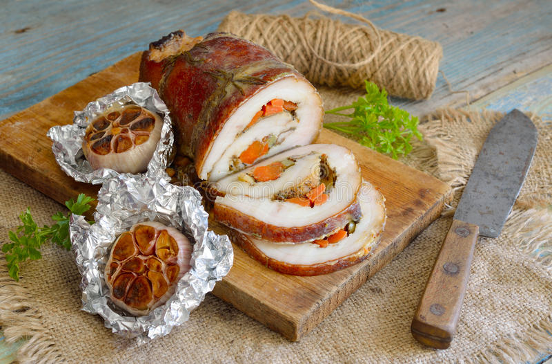 Rôti bourré d'échine de porc avec l'ail cuit au four image libre de droits