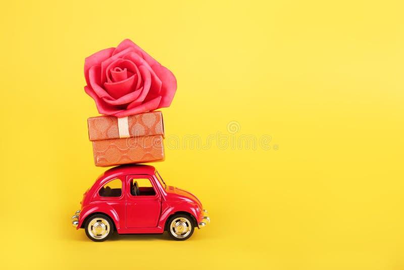 R?tro voiture rouge de jouet avec la fleur rose rouge sur le fond jaune Fleurs, concept de la livraison de cadeaux image stock