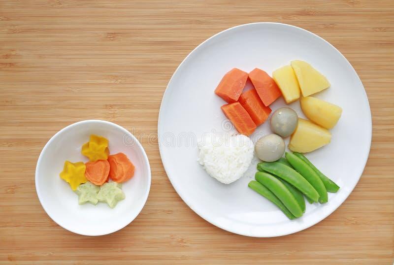 R?tt av kokta gr?nsaker behandla som ett barn matmoroten, ?gget, potatisen, ris, och den s?ta ?rtan i den vita plattan med mosat  royaltyfria foton