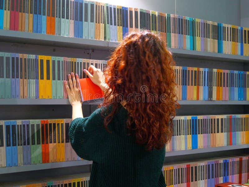 R?tt haired f?r kvinnlig ton?ring v?lja en bok i f?rgrik bokhandel fotografering för bildbyråer