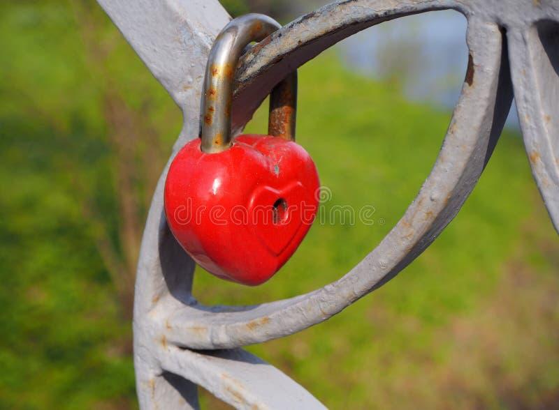 R?tt hj?rtal?s f?r gammal rostig metall, det romantiska symbolet av aldrig att avsluta f?r?lskelse som h?nger p? staketet av bron royaltyfri foto