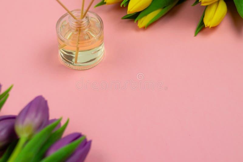 R?ucherst?bchen und Tulpen auf rosa Hintergrund stockbilder