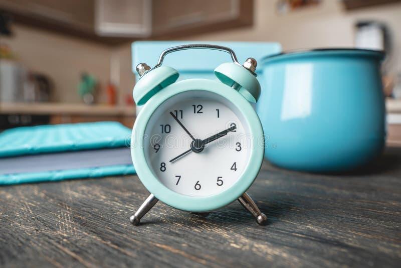R?veil bleu en m?tal sur la table avec une tasse et un journal intime sur le fond de la cuisine Temps et mode ? la maison photos libres de droits