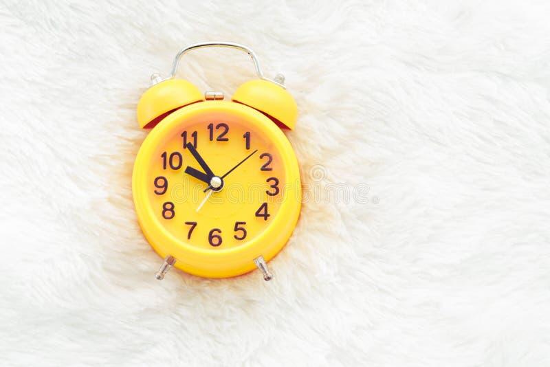 R?veil jaune sur la laine blanche Concept en retard et paresseux de temps Matin dans le th?me de vacances Horloge d'environ 10 O photographie stock