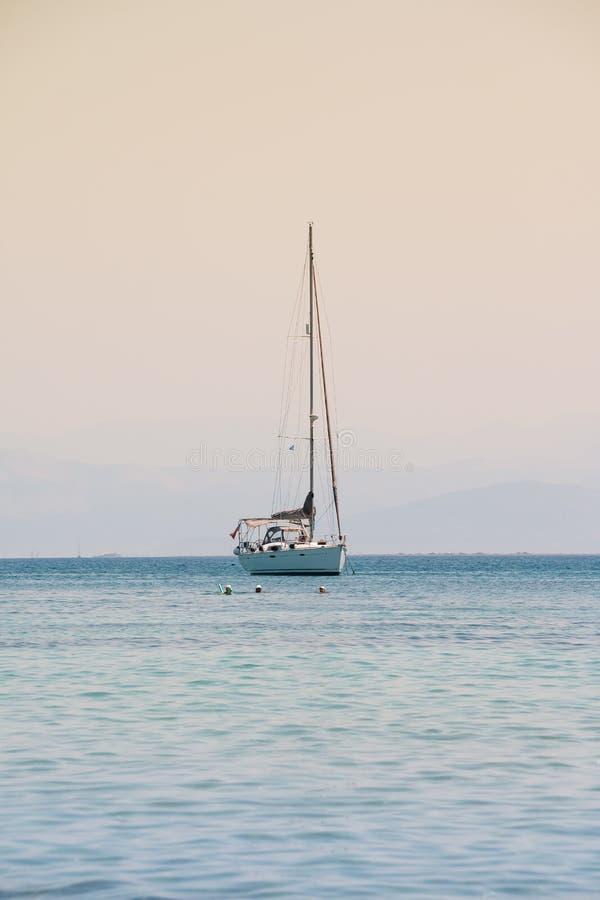 Raça de iate da navigação yachting sailing Iate só com a vela branca no mar aberto no por do sol Barco só azul fotos de stock royalty free