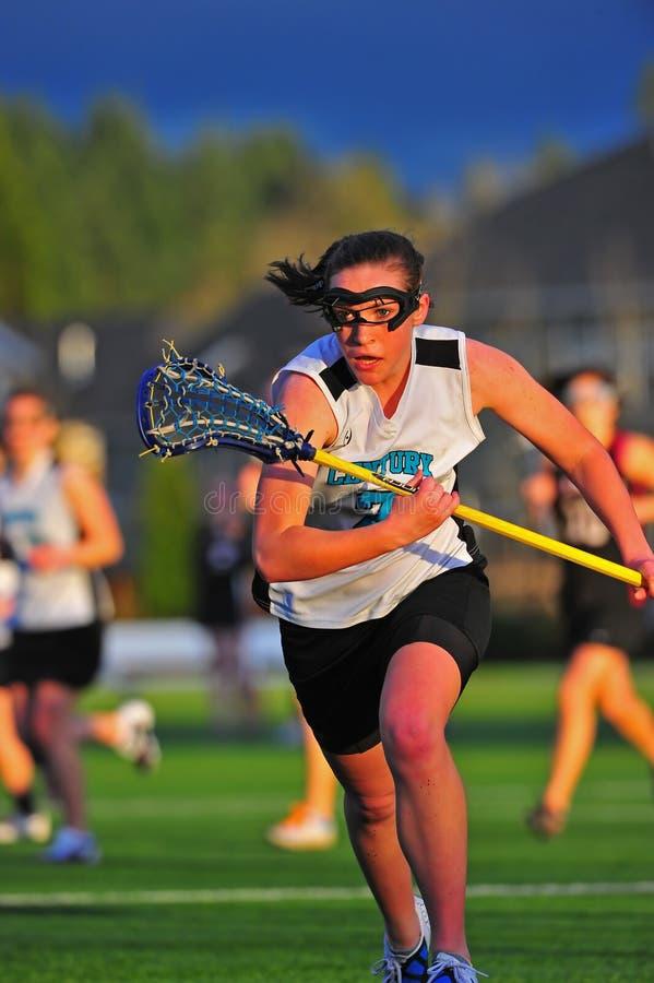 Raça do Lacrosse das meninas após a esfera imagem de stock