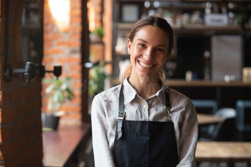Raça misturada feliz fêmea no avental que sorri olhando a câmera foto de stock royalty free