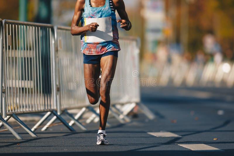 Raça running da maratona, pés africanos da mulher na estrada do outono Corredor africano que corre a maratona urbana o na cidade imagens de stock