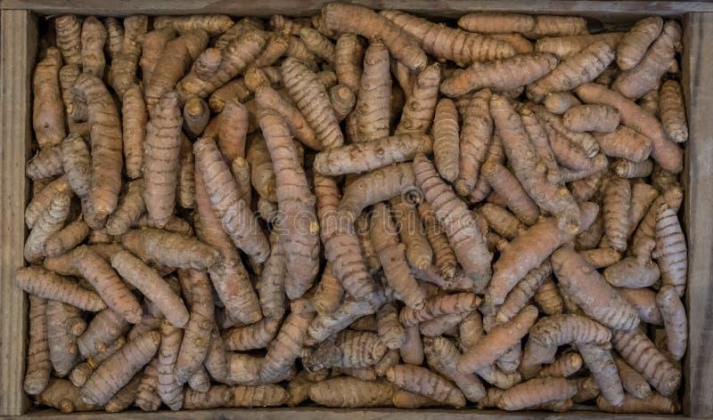 Raíces de cúrcuma en una caja de madera, fotografiada desde arriba La cúrcuma es una especia de cocinar y tiene una variedad de p fotografía de archivo