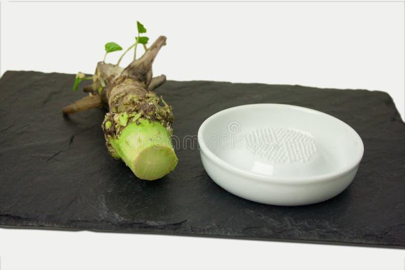 Raíz fresca del Wasabi con la amoladora de cerámica fotos de archivo