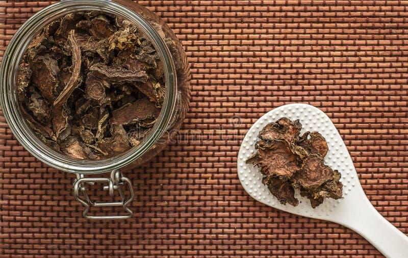 Raíz seca cortada del rosea de Rhodiola en un tarro de cristal en fondo blanco natural fotografía de archivo