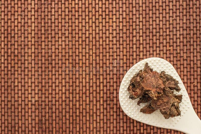 Ra?z seca cortada del rosea de Rhodiola en un tarro de cristal en fondo blanco natural imagen de archivo