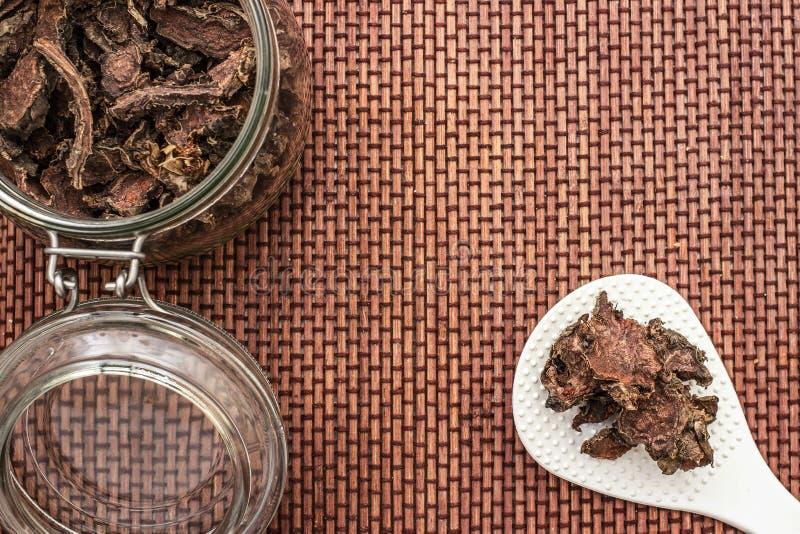 Ra?z seca cortada del rosea de Rhodiola en un tarro de cristal en fondo blanco natural imágenes de archivo libres de regalías